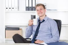Young smiling man is drinking a cup of coffee in the office Royalty Free Stock Images