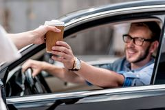young smiling man driving car and taking stock photos