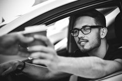 Young smiling man driving car and taking away coffee. Portrait of man sitting in car and buying coffee to go royalty free stock photography