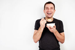 Young smiling man eating cereal Royalty Free Stock Photos