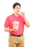 Young smiling man eating popcorn Stock Images