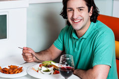 Young smiling man eating at restaurant Stock Photo