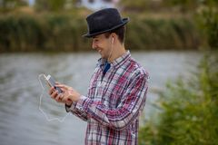 Young smiling man in fashionable clothes listens to music Royalty Free Stock Photography