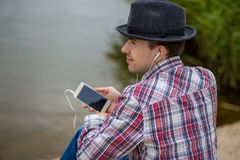 Young smiling man in fashionable clothes listens to music Stock Photo