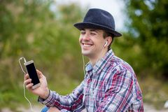 Young smiling man in fashionable clothes listens to music Stock Photography