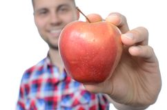 Young smiling man with fresh apple. Isolated on white Royalty Free Stock Photography