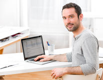 Young smiling man in front of a computer. View of a Young smiling man in front of a computer Royalty Free Stock Image