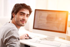 Young smiling man in front of computer Royalty Free Stock Images