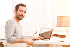 Young smiling man in front of a computer Royalty Free Stock Photos