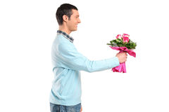Young smiling man giving flowers Royalty Free Stock Photo