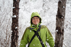 Young smiling man in glasses and green sports jacket with hood s. Tands in winter forest with falling snow around stock photos