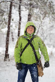 Young smiling man in glasses and green sports jacket with hood s. Tands in winter forest with falling snow around royalty free stock photography