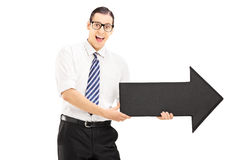 Young smiling man with glasses holding a big arrow and pointing Royalty Free Stock Photos