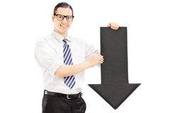 Young smiling man with glasses holding a big black arrow pointin Stock Images