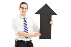 Young smiling man with glasses holding a big black arrow pointin Royalty Free Stock Photo