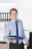 Young smiling man is handing over a file Royalty Free Stock Photo