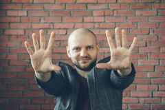 Young smiling man with hands in air to say stop or hypnotist gesture. Selective focus Royalty Free Stock Photography