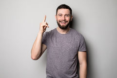 Young smiling man having a good idea isolated on white. Copy space and t shirt. Finger up. Selective focus. Royalty Free Stock Photos