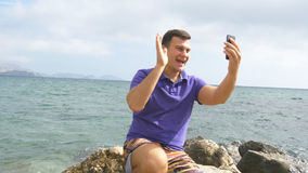Young smiling man having a video call on smart phone at the sea beach. Happy guy making video online chats on beautiful Stock Image