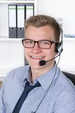 Young smiling man with headset in the office Stock Image