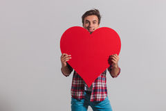 Young smiling man hides behind a big red heart. On grey studio background Stock Photos