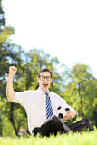 Young smiling man holding a ball and gesturing happiness in the Royalty Free Stock Photo