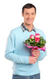 Young smiling man holding a bouquet of flowers Stock Image