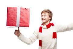Young smiling man holding christmas gift. Portrait of young cheerful smiling caucasian man which balancing red christmas gift on thumb with happy smile stock images