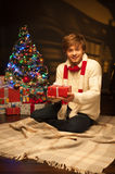 Young smiling man holding red christmas gift Stock Image
