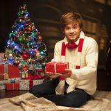 Young smiling man holding red christmas gift Royalty Free Stock Photos