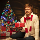 Young smiling man holding red christmas gift Royalty Free Stock Images