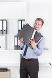 Young smiling man is holding several files in the office Stock Photography