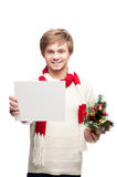 Young smiling man holding sign. Portrait of young cheerful smiling caucasian man which holding sign and christmas tree with nice smile Royalty Free Stock Photo