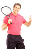 Young smiling man holding a tennis racket and giving thumb up Stock Photography