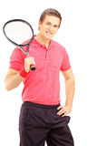 Young smiling man holding a tennis racket and posing Royalty Free Stock Image