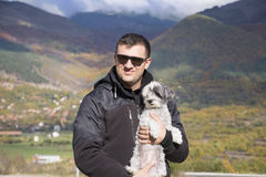 Young smiling man hugging his small white dog in the autumn mountain Stock Image