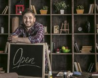 Young smiling man leather worker standing near open sign at table with tools Stock Photos