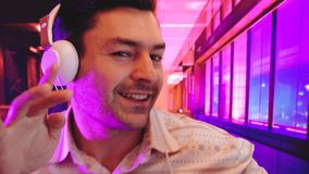 Young smiling man listening to music with earphones and dancing isolated interior background with Cool Neon Lights like stock video