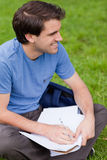 Young smiling man looking away while working on the grass Royalty Free Stock Photos