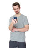 Young and smiling man looking at his cellphone Stock Photography