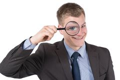 Young smiling man is looking through magnifier Stock Images
