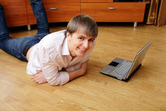 Young smiling man lying on the floor with laptop Royalty Free Stock Images