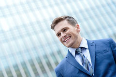 Young smiling man on modern building background Royalty Free Stock Image