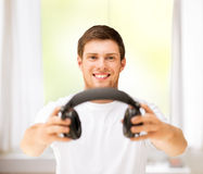 Young smiling man offering headphones at home Stock Photo