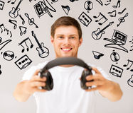 Young smiling man offering headphones Stock Photography