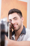 Young smiling man pointing guitar at you Stock Image