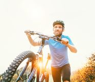 Young smiling man pushing a mountain bike up the hill. Active ad royalty free stock images