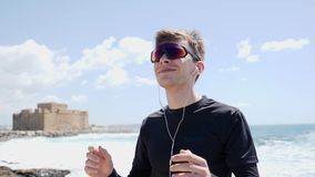 Young smiling man puts in earphones and shakes his head while listening to the music. Man wearing black outfit on the beach. Slow stock video