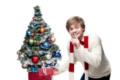 Young smiling man puts gift under christmas tree. Portrait of young cheerful smiling caucasian man which placing christmas gift under the christmas tree with Stock Photo