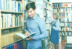 Young smiling man reading book while. Young smiling cheerful  men reading book while choosing it in book shop Royalty Free Stock Image